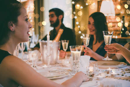 luxuries: Friends celebrating Christmas or New Year eve. Party table with champagne. Stock Photo