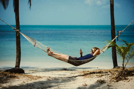 A young man relaxes in a hammock at the beach while checking messages on his smartphone. Toned image Banque d'images