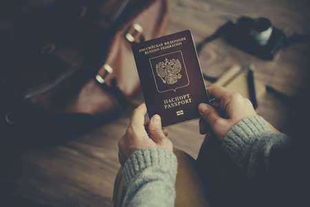 Person holds Russian travel passport in hands with leather bag and photo camera in the background. Travel and tourism concept. Toned picture Фото со стока