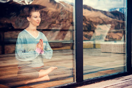 Young beautiful woman meditating while practicing yoga with mountain view in the window reflection. Freedom concept. Calmness and relax, woman happiness. Toned picture