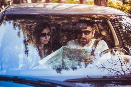 Joven y mujer celebrar la hoja de ruta en un coche. Viajes y concepto de la aventura. Imagen en tonos