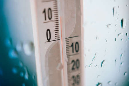 rain weather: Closeup photo of household alcohol thermometer showing temperature in degrees Celsius with rain drops on glass. Cold weather and forecast concept