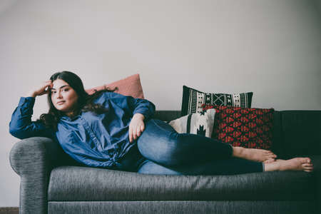 Beautiful plus size girl lying on the sofa. Toned picture