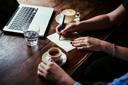 business ideas: Two women discussing business projects in a cafe while having coffee. Startup, ideas and brain storm concept Stock Photo