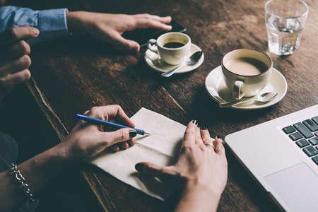 Dos mujeres hablando de proyectos empresariales en un café mientras que el café. De inicio, ideas y concepto de lluvia de ideas. cuadro entonado