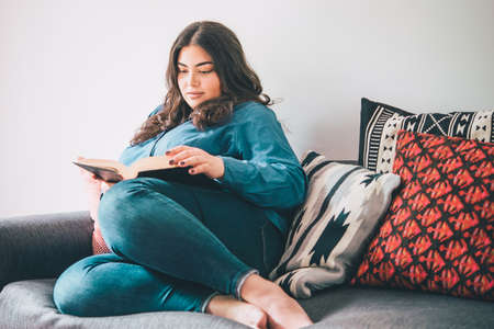 Beautiful woman sitting on sofa reading a book. Toned picture Stock fotó - 73302633