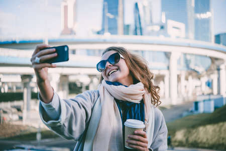 Young beautiful woman takes a selfie with Moscow City international business center in the background.