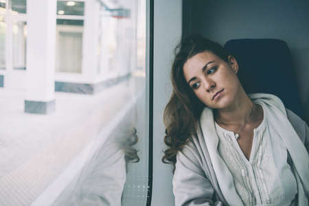 femme triste: Young sad woman looking through the train window. Toned picture Banque d'images