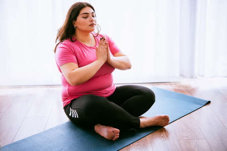 Beautiful plus size girl meditating indoors. Yoga and wellness concept Stockfoto