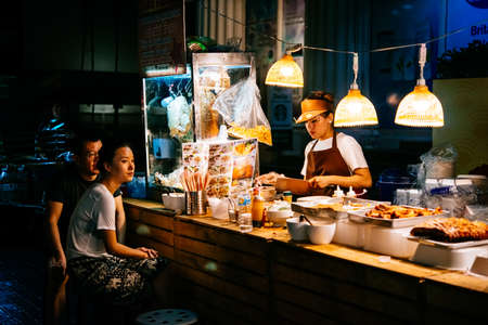 BANGKOK, THAILAND - FEBRUARY 26, 2016: People are buying food at night street food market in Bangkok, Thailand. Reklamní fotografie - 75697851