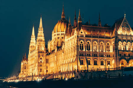 View of the Parliament building lit by the evening lights in Budapest, Hungary. Banco de Imagens - 83839201