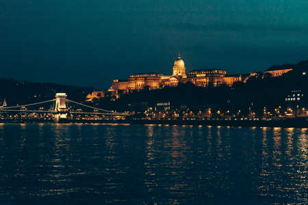 View of the Castle hill lit by the evening lights seen from the Danube river in Budapest, Hungary.