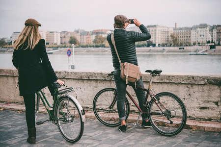 한 부부는 헝가리 부다페스트에있는 다뉴브 강 제방에서 자전거 타기를 즐깁니다. 색조 사진