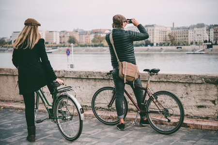 A couple enjoys bicycle ride on the Danube river embankment in Budapest, Hungary.  Toned picture 版權商用圖片
