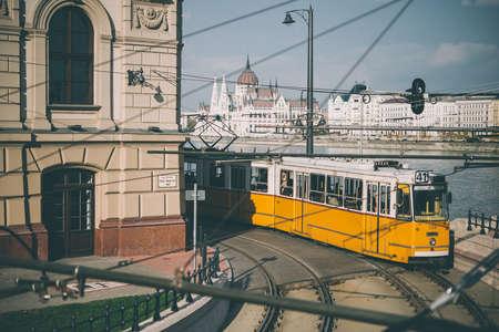 トラムは、ブダペストの通りの 1 つに沿って行きます。バック グラウンドで見られる国会議事堂。トーンの画像