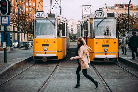 若い女性は、トラムの停留所、ハンガリー ブダペストで通りを渡る。
