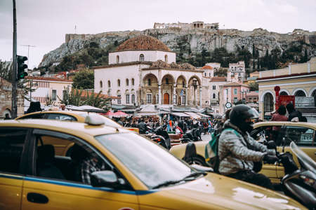 View of the Monastiraki square busy with people and traffic in the evening. The view of Acropolis hill, Athens, Greece. Editöryel