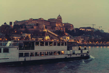 View of the Castle hill seen from the Danube river in the evening in Budapest, Hungary.