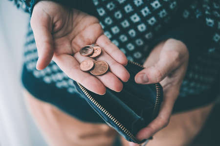 Hands holding euro cent coins and small money pouch. Toned picture Stock Photo