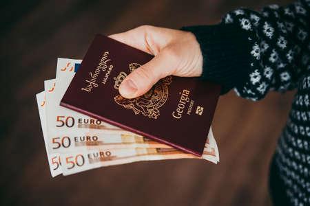 Hand met paspoort van Georgië en euro rekeningen