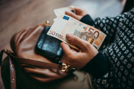 Girls hands holding euro bills, small money pouch and leather bag
