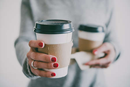 Two take-away cupsof  coffee in hands. Toned image Stock Photo