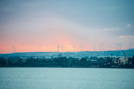 The view of windmill electric powerplants seen at the sunset.