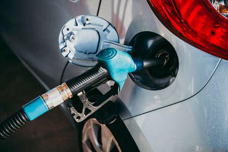 Fuel pump filling a car at a petrol station.