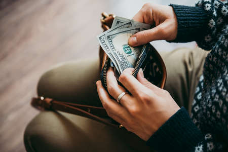 Girls hands holding dollar bills, small money pouch and leather bag