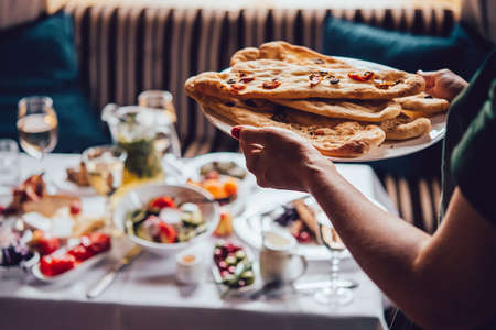 Hands holding a plate with bread of focaccia served during a dinner of a party at home or in a restaurant.  Toned picture