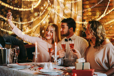 Friends making selfie while celebrating Christmas or New Year eve. Party table with rose champagne. Foto de archivo
