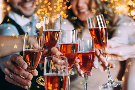Friends celebrating Christmas or New Year eve with glasses of rose champagne