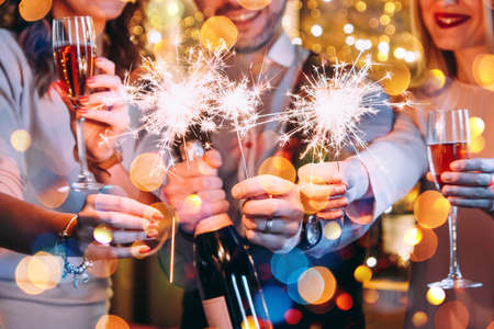 Friends celebrating Christmas or New Year eve with Bengal lights. Stock Photo