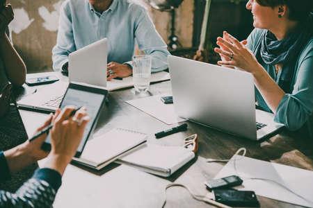 Laptop, telefon komórkowy, tablet i dokumenty na stole roboczym w kreatywnym biurze. Pomyślna praca zespołowa i koncepcja uruchomienia biznesu. Stonowany obraz