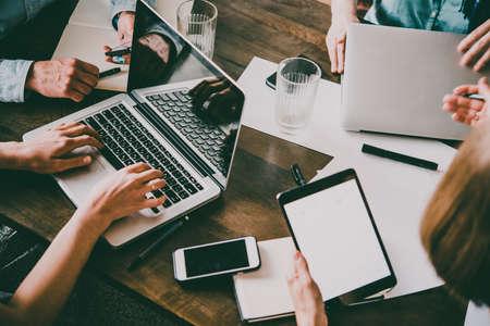 クリエイティブオフィスの作業テーブルにノートパソコン、携帯電話、タブレット、ドキュメント。成功したチームワークとビジネススタートアッ 写真素材