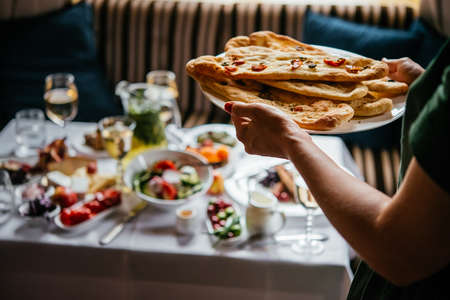 Hands holding a plate with bread of focaccia served during a dinner of a party at home or in a restaurant.