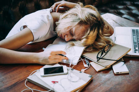 A tired teenage girl sleeping on her table while doing her school homework. Laziness and procrastination concept