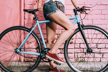 Young beautiful girls legs and single speed of fixed gear bicycle with a bright wall in the background. Stock Photo