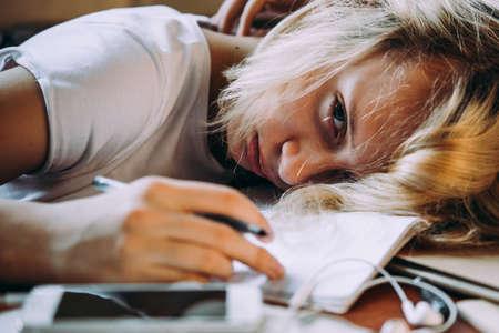 Eine müde Jugendliche, die auf ihrem Tisch schläft, während sie ihre Schulhausaufgaben macht. Konzept der Faulheit und des Aufschubs