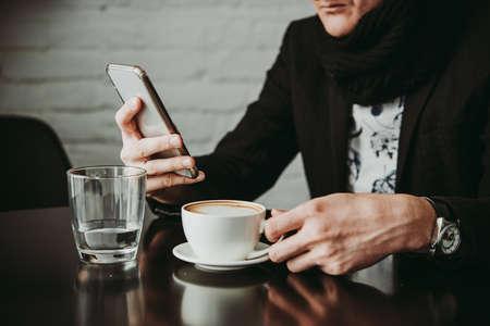 카페에서 스마트 폰과 카푸치노 커피 잔을 들고 남자 스톡 콘텐츠 - 96908158