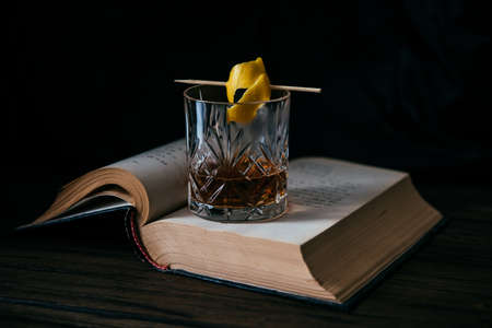 Glass of whiskey or cocktail and old book 스톡 콘텐츠