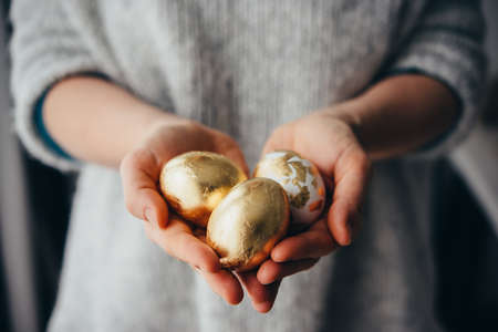 Hands holding modern style golden foil coated easter eggs. Stok Fotoğraf - 96908173