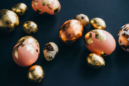 Modern style easter eggs coated with golden foil. on a dark background Фото со стока