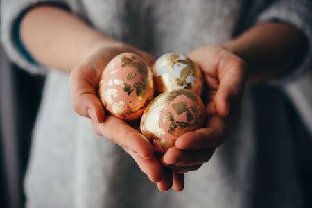 Hands holding modern style golden foil coated easter eggs.