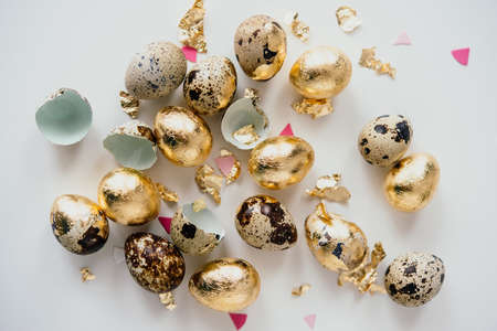 Modern style quail easter eggs coated with golden foil.