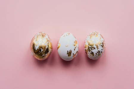 Modern style easter eggs coated with golden foil on a pink background Stok Fotoğraf