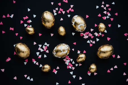 Modern style easter eggs coated with golden foil. on a dark background Stok Fotoğraf - 96908249