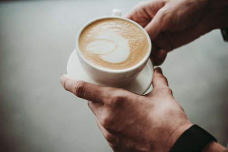 Man holding cup of cappuccino coffee in hands Stock Photo