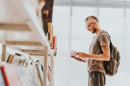Mature handsome man choosing books at a library or a book store.
