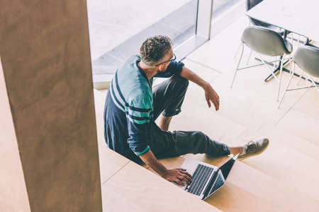 Mature handsome man sitting at the steps working on his laptop.